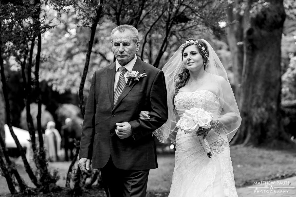 Bride walking with her father at wedding ceremony