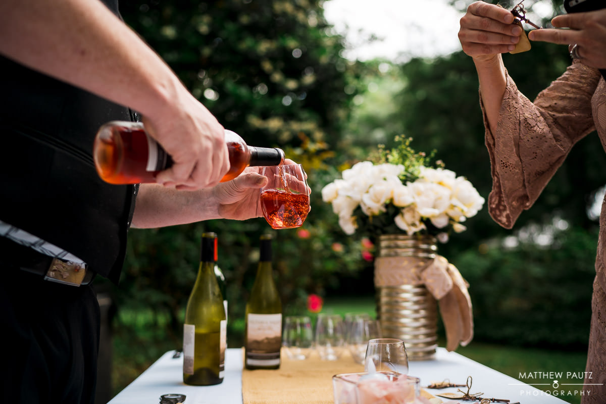 bartender pouring wine at wedding cocktail hour