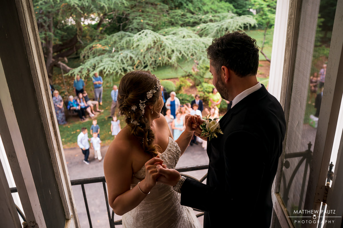 bride and groom dancing on balcony before wedding reception at the duncan estate