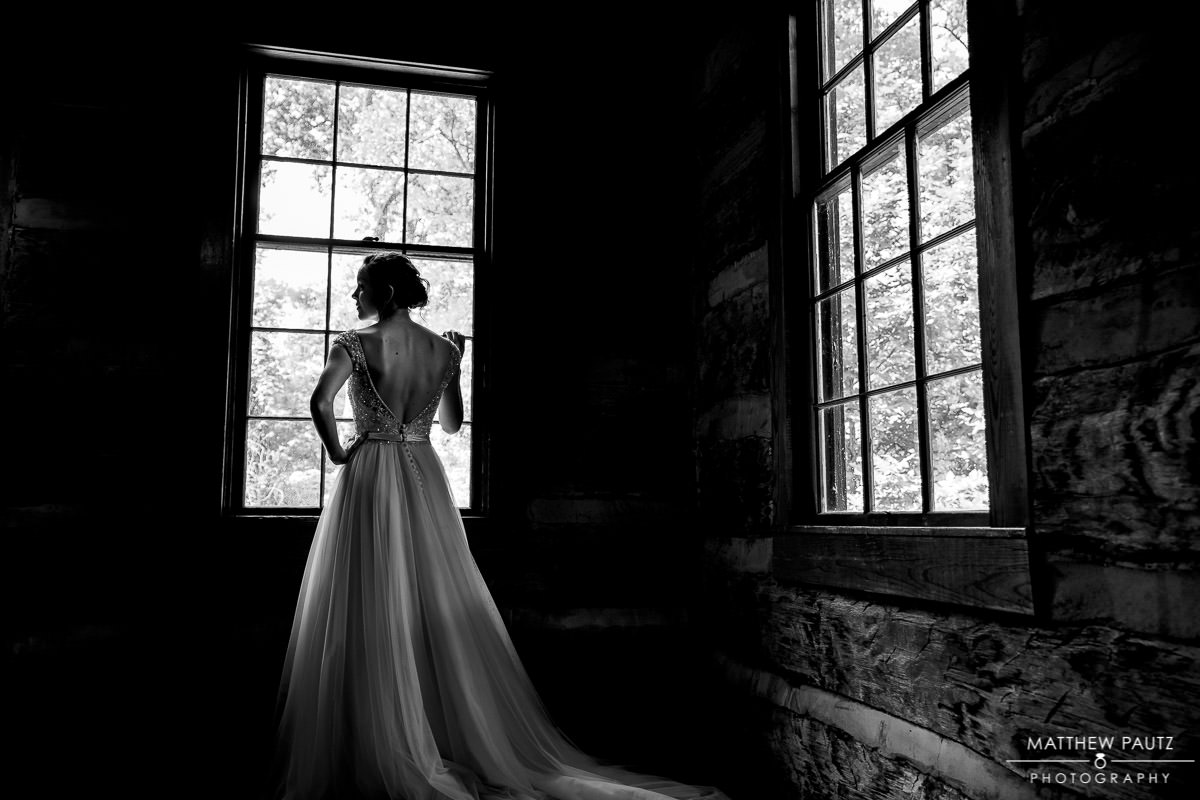 bride looking out window at Table Rock Lodge before wedding day