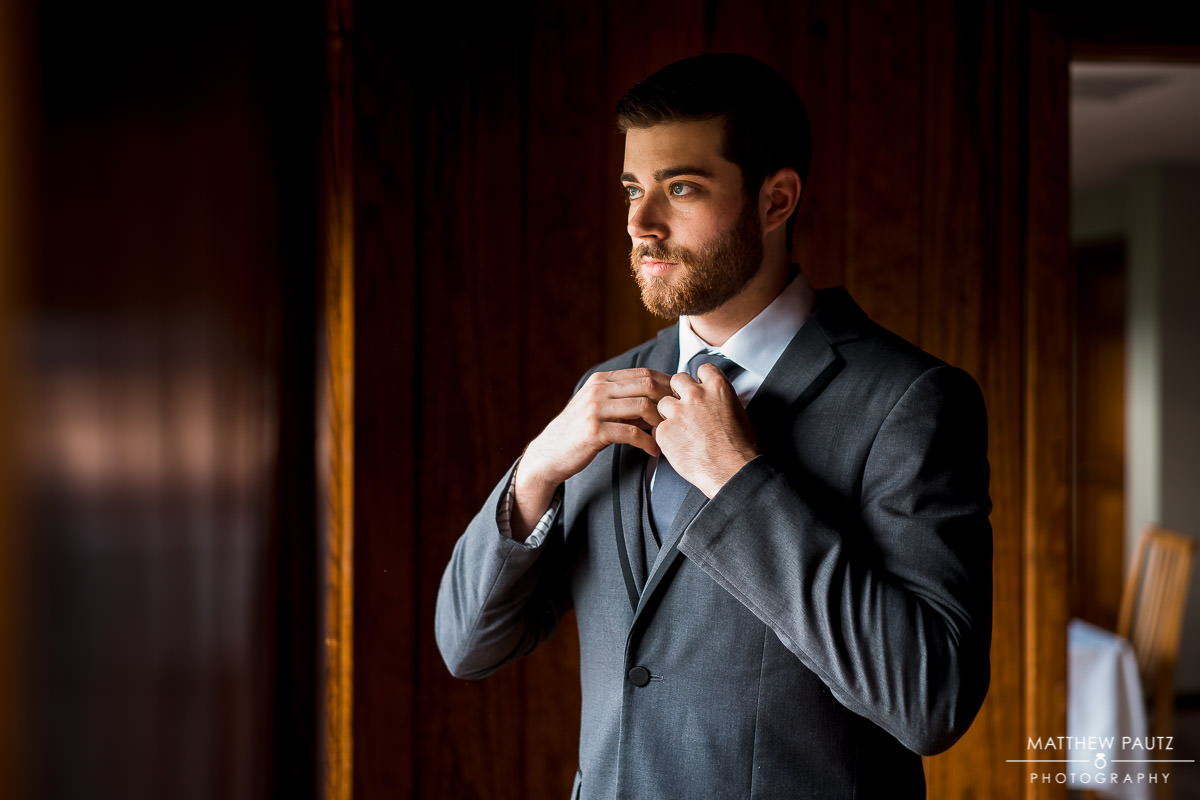 groom getting dressed at table rock lodge before wedding