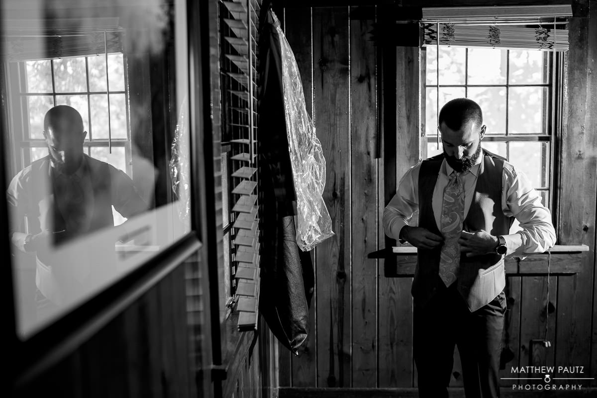 Groom getting dressed at Table Rock Cabin