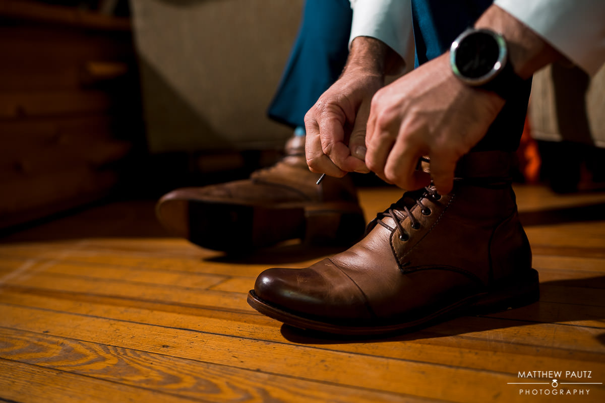 Groom putting on shoes before wedding ceremony