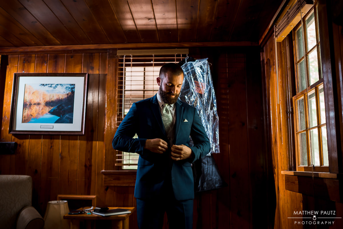 groom getting dressed for wedding at table rock cabins