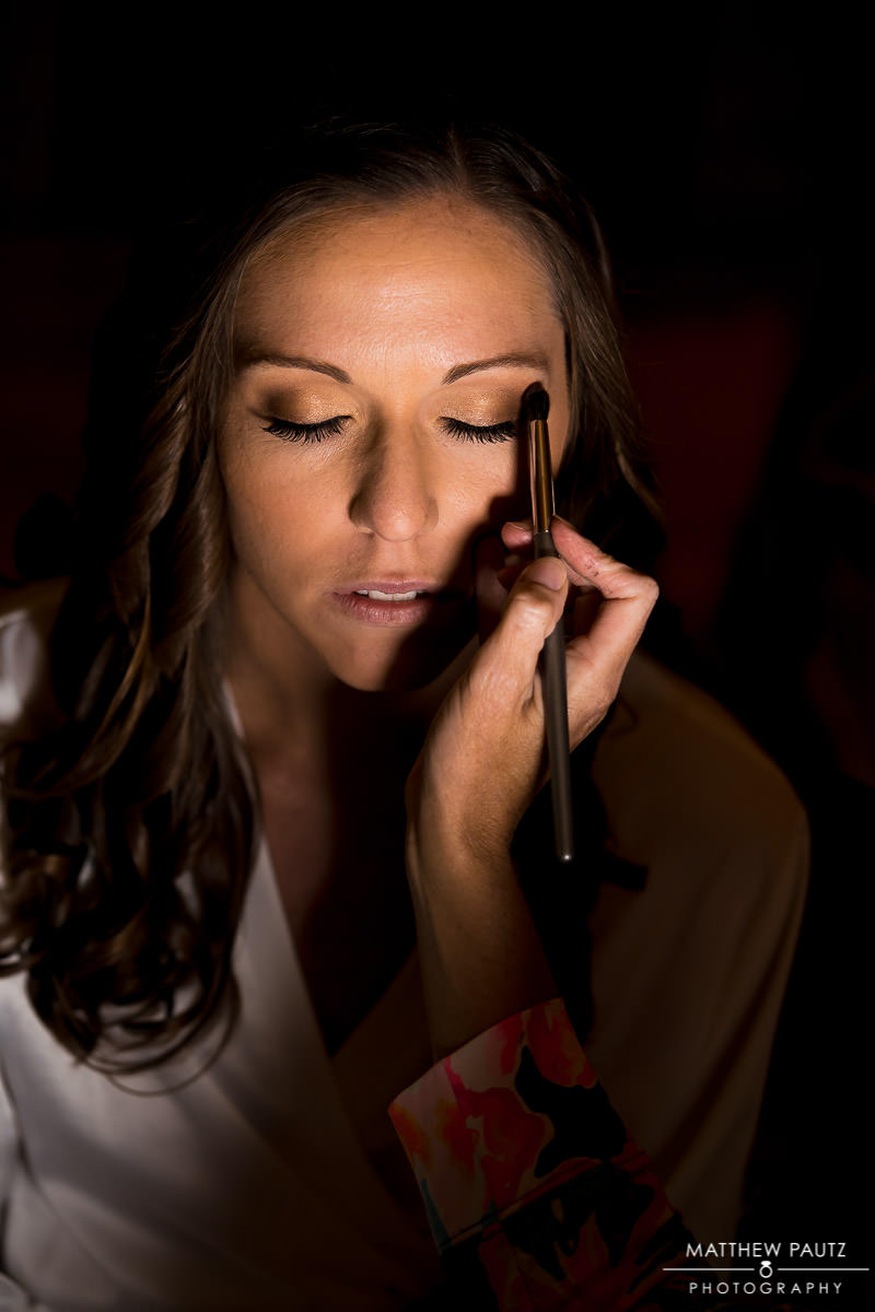 closeup photo of bride having makeup applied