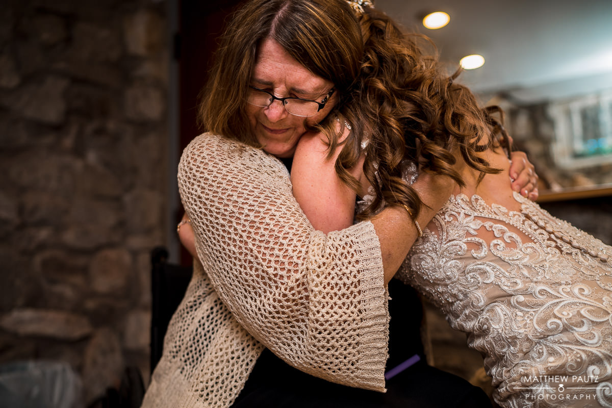 bride hugging close friend before mountain wedding ceremony