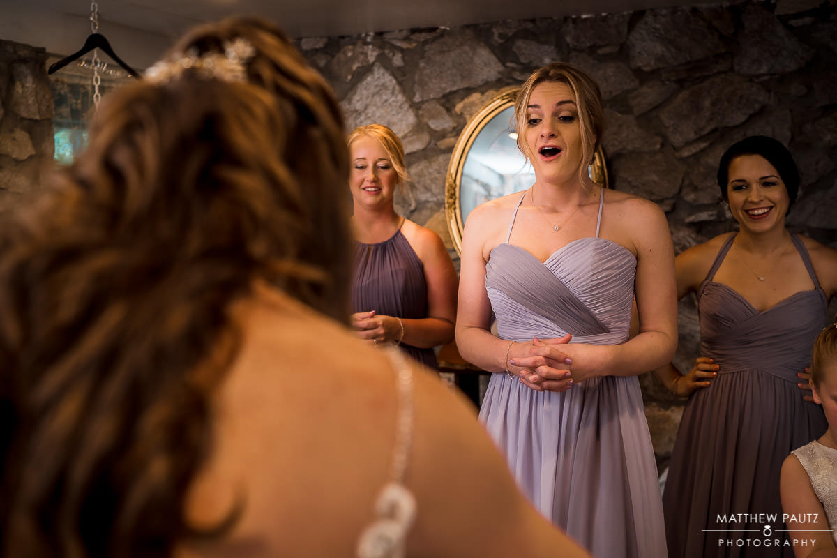bridesmaids reacting to seeing bride in wedding dress