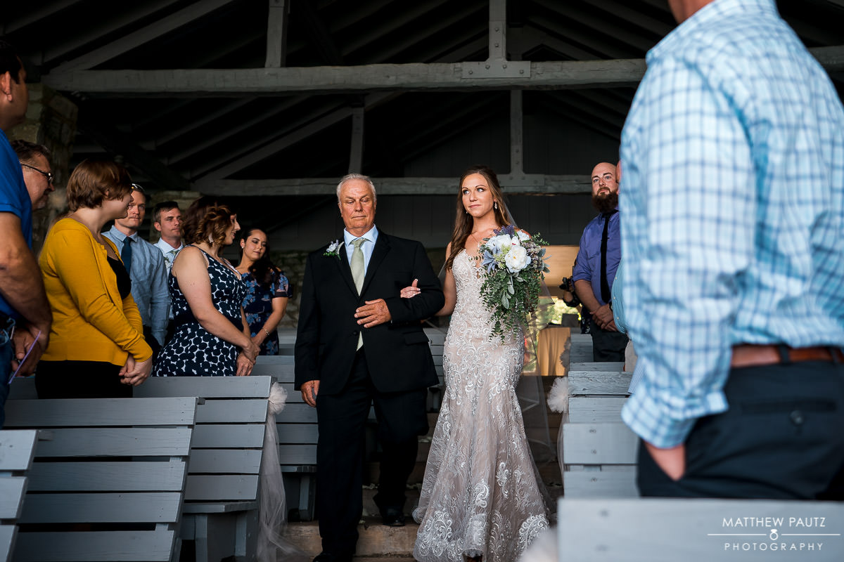 bride walking down aisle with father at mountain wedding ceremony