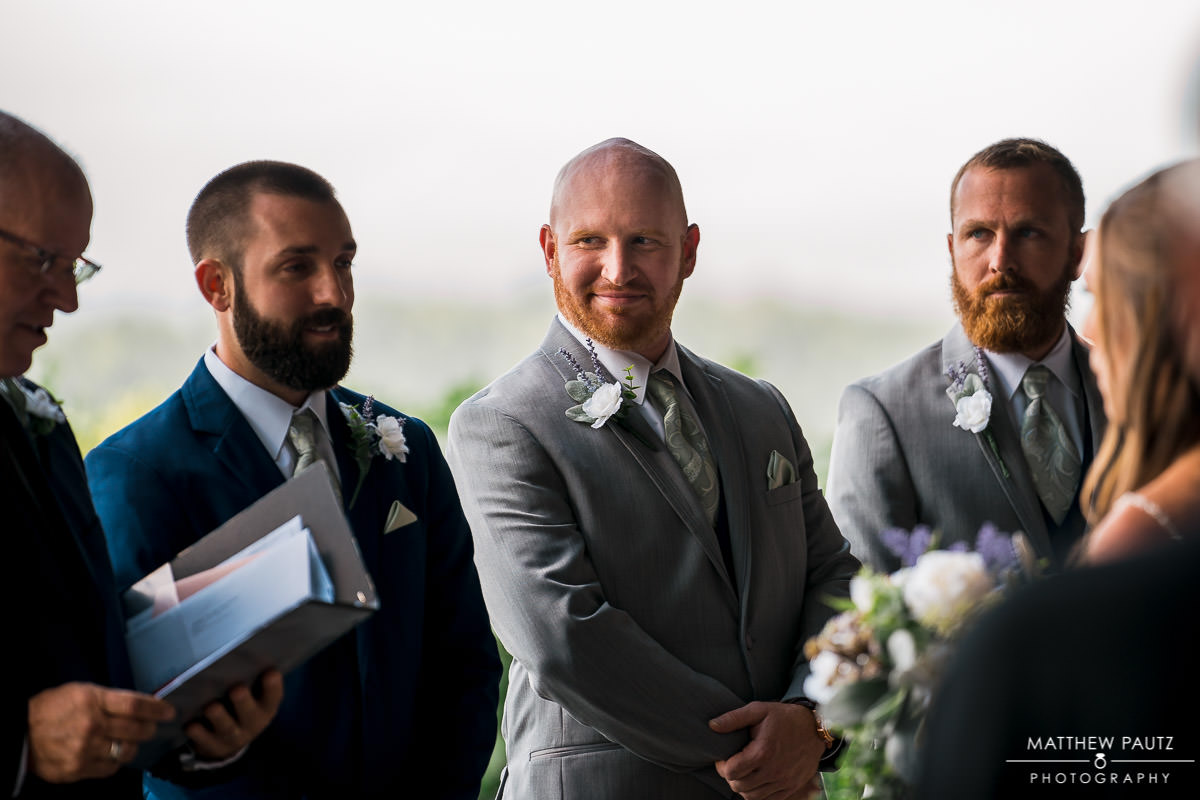 groomsman watching groom's reaction during wedding ceremony