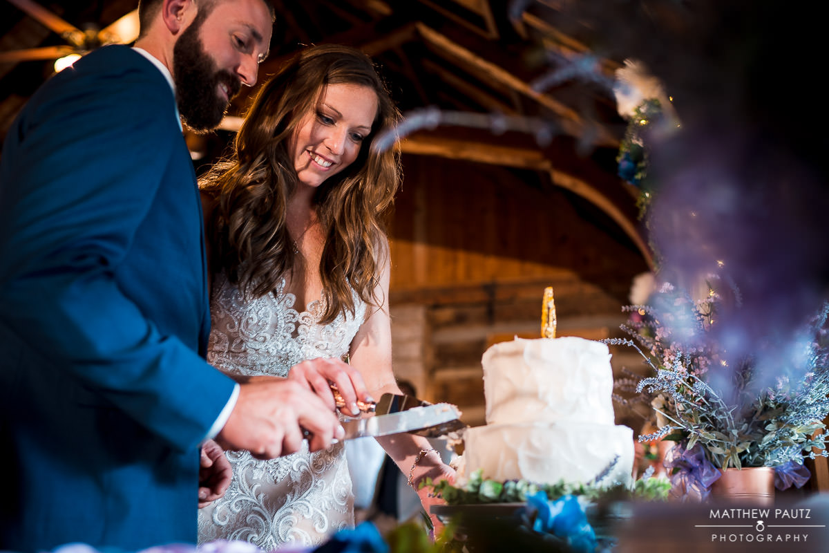bride and groom cutting wedding cake in mountain lodge