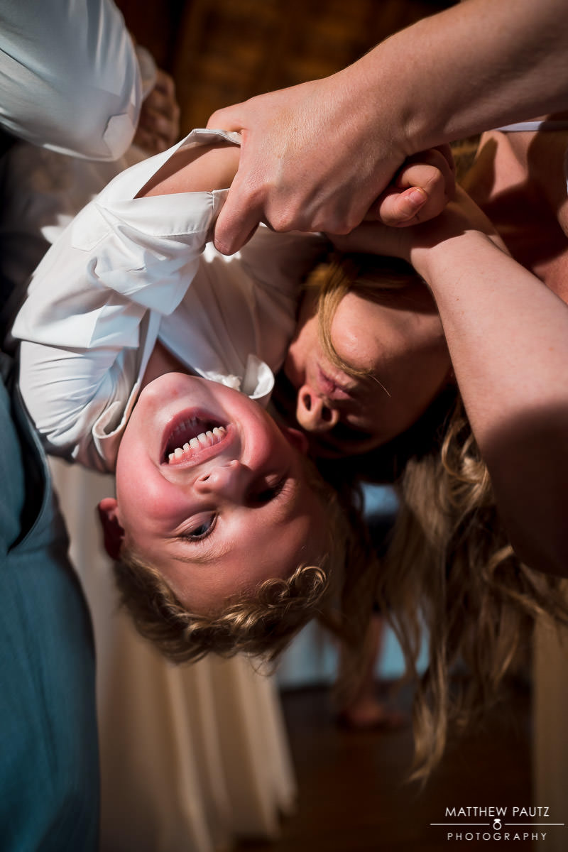 ring bearer being held upside down during wedding reception