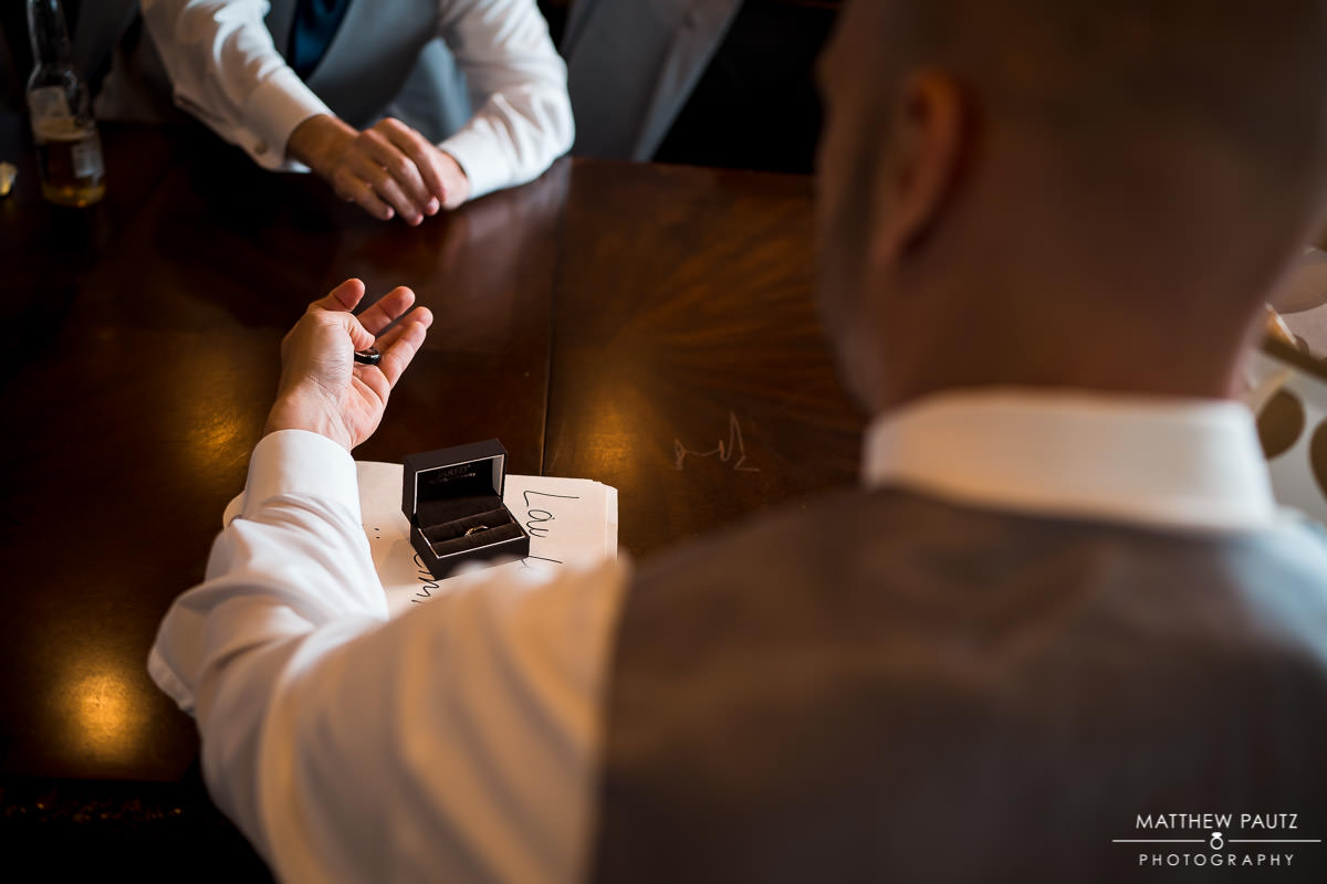 groom holding looking at wedding ring while holding it before ceremony