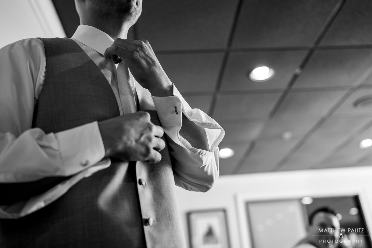 groom adjust tie at Cliffs at Glassy Clubhouse