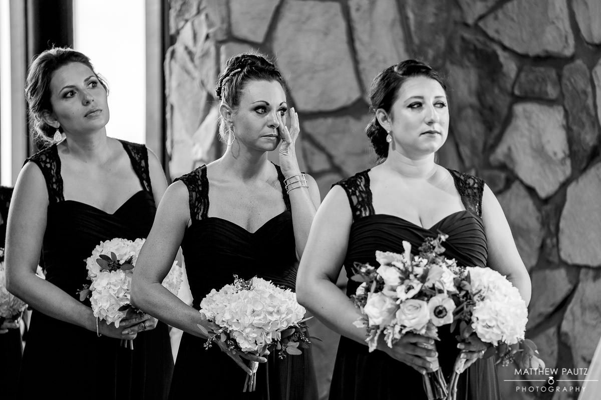 bridesmaid wiping away tear at wedding ceremony