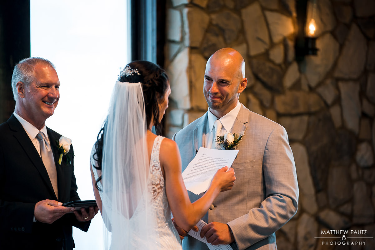 groom reacts as bride reads vows during wedding ceremony