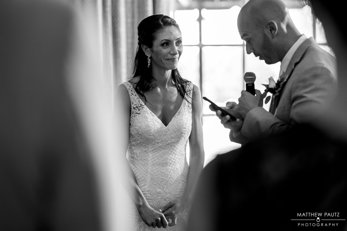 bride watches as groom reads speech at wedding reception