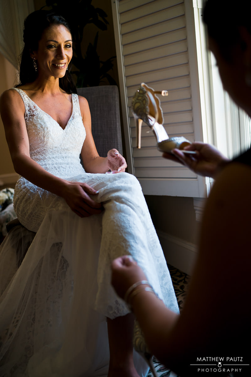 bridesmaid helping bride get dressed before wedding