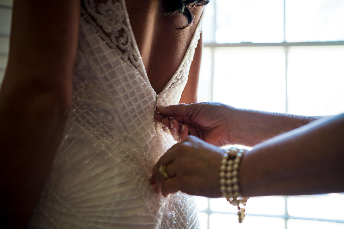 bride putting on dress at Green Valley Country Club