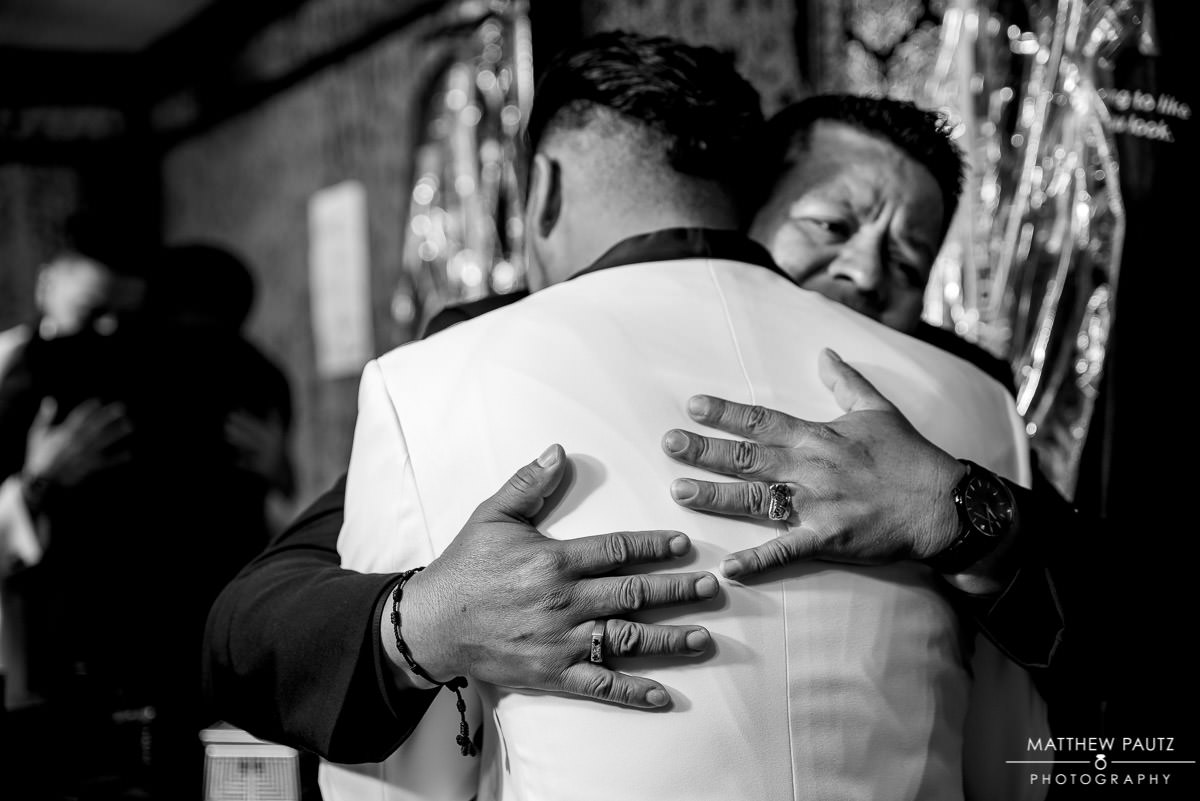 groom hugging his father before wedding ceremony