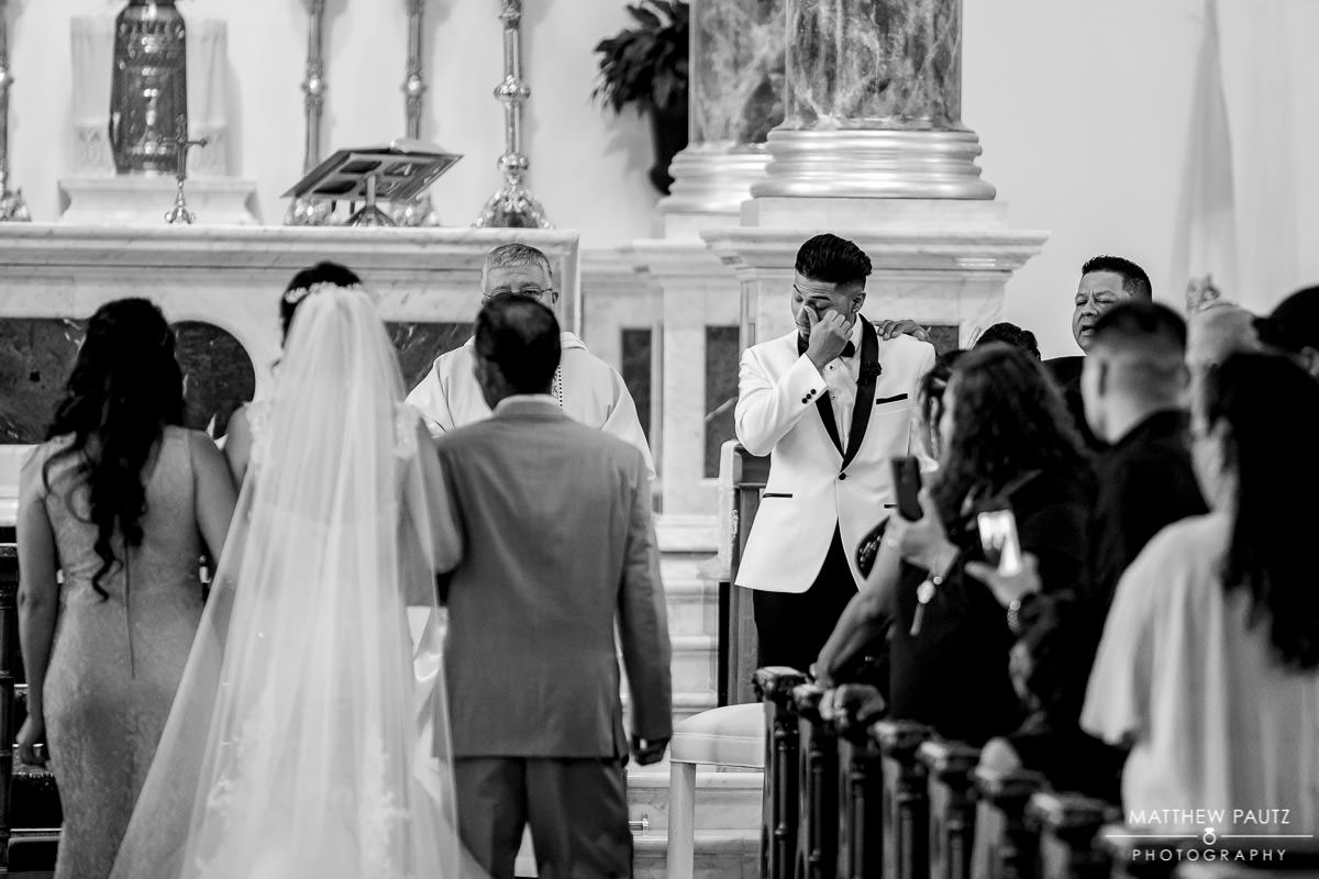 groom crying seeing bride walking down the aisle at wedding ceremony