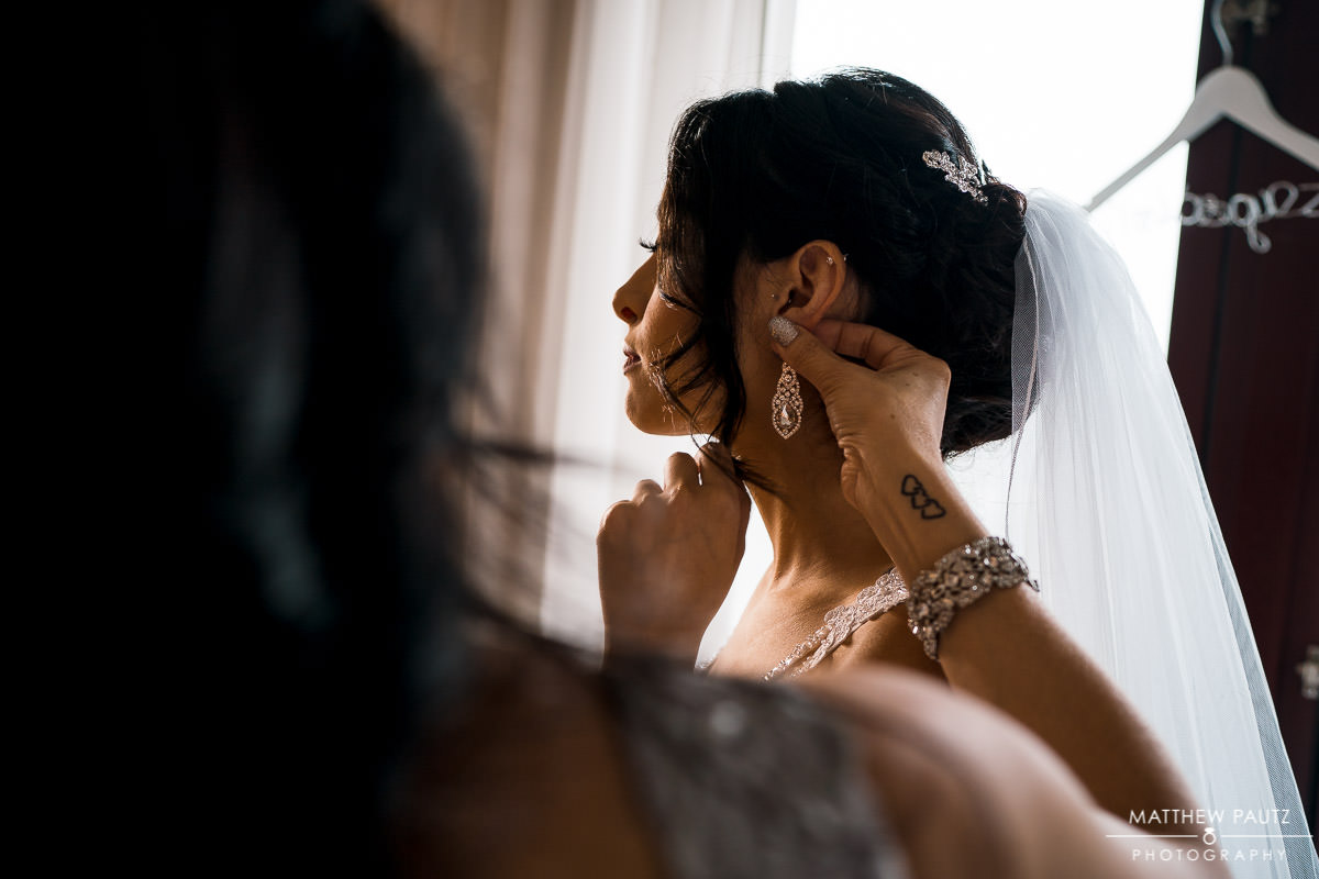 bride getting help putting earrings on before wedding