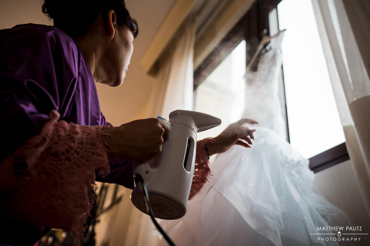 Mother of the groom steaming the bride's wedding dress