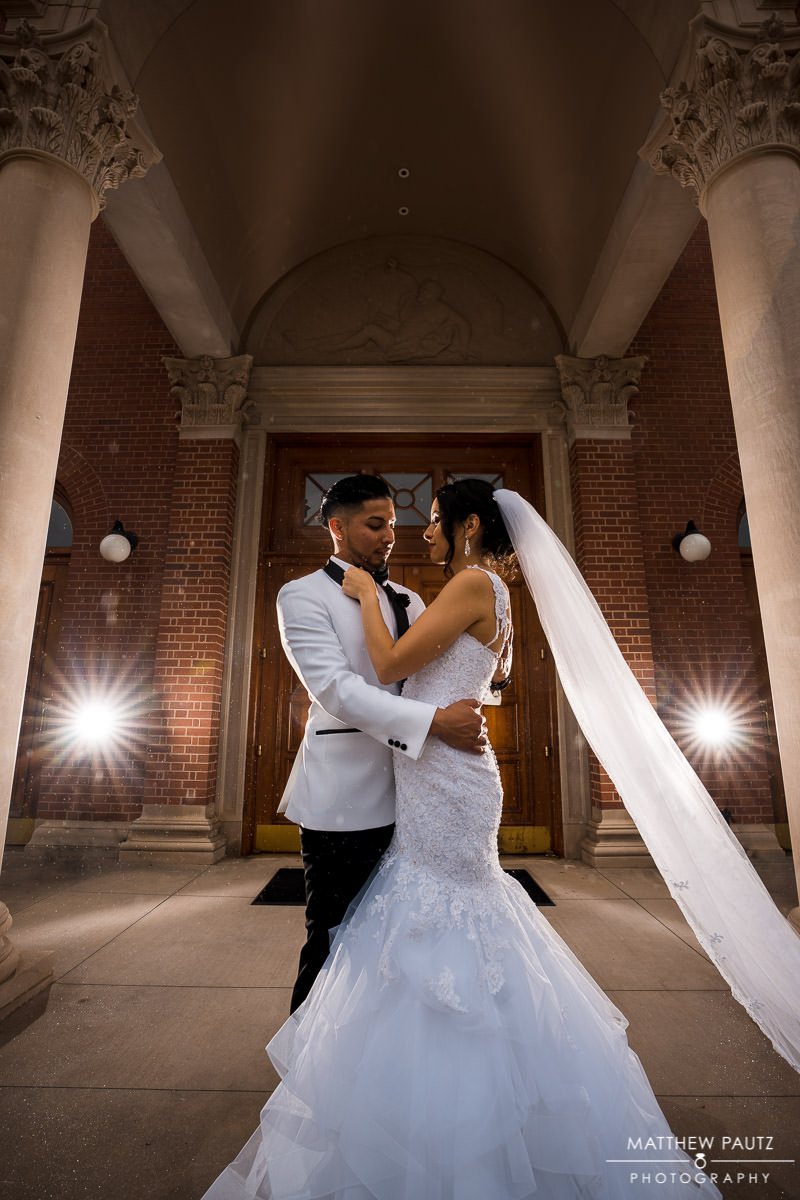 dramatic couple's photo outside catholic church after wedding ceremony