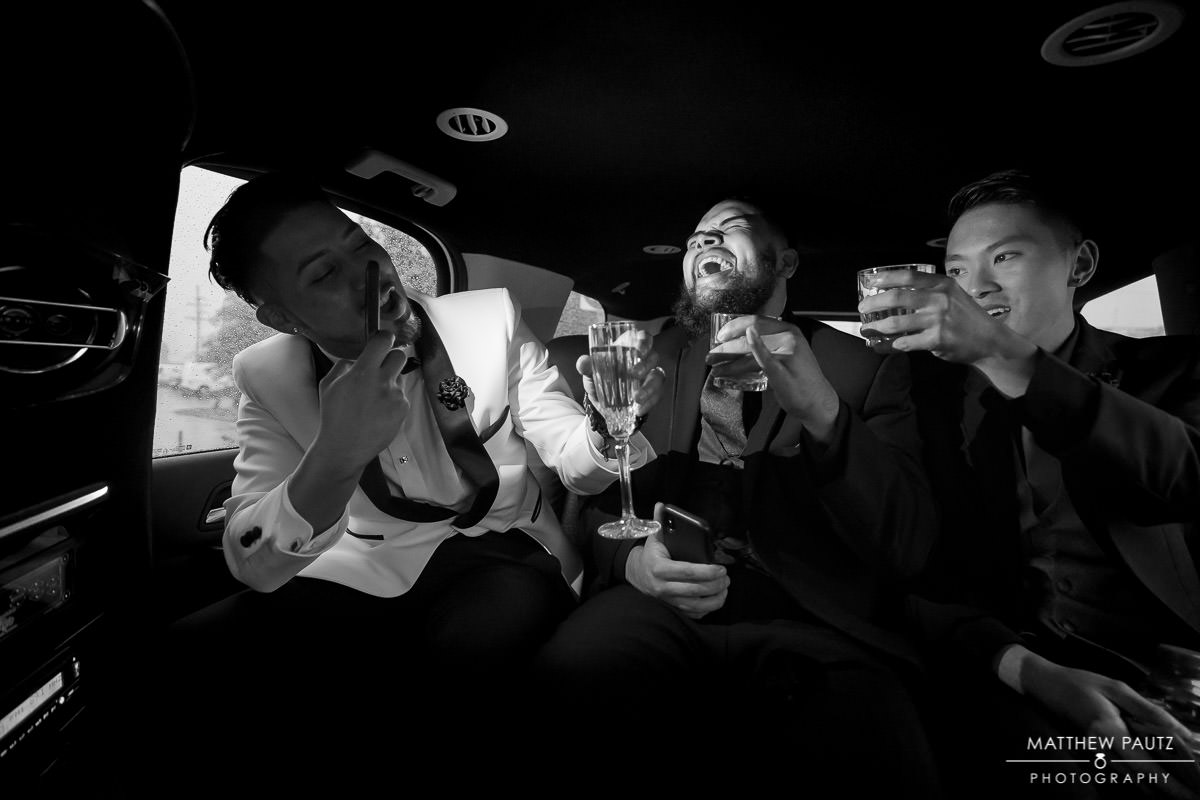 groomsman drinking and having fun in limo ride to wedding reception