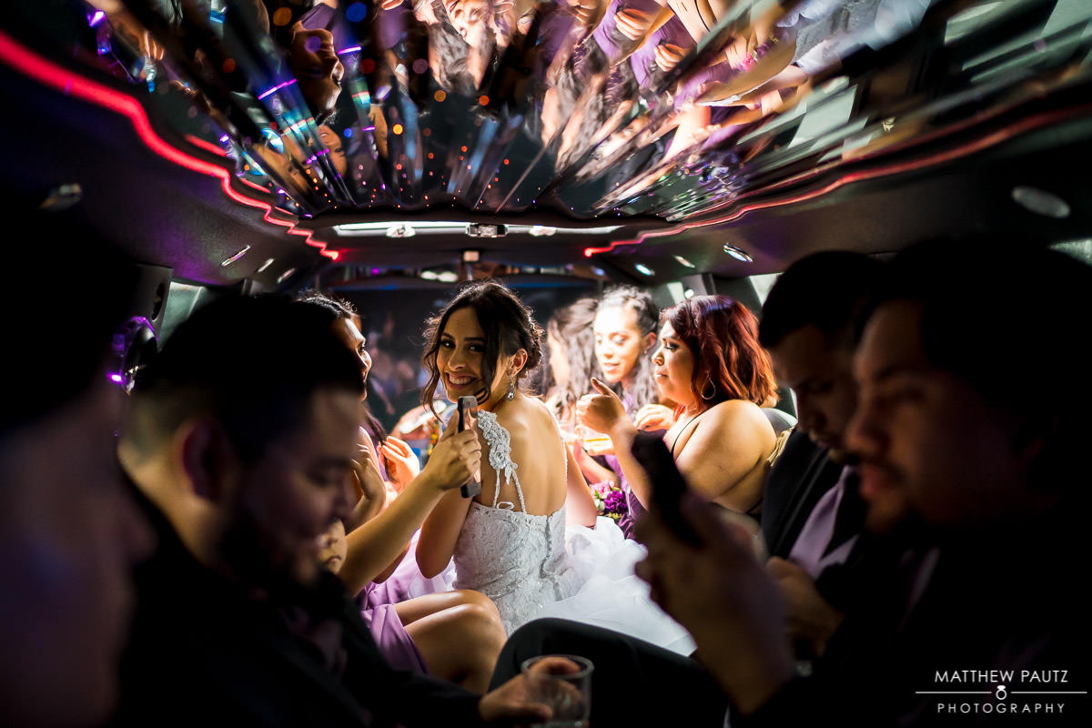 bride and wedding party hanging out in limo on the way to reception