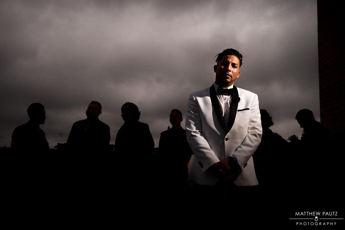 dramatically lit groomsman group photo after wedding