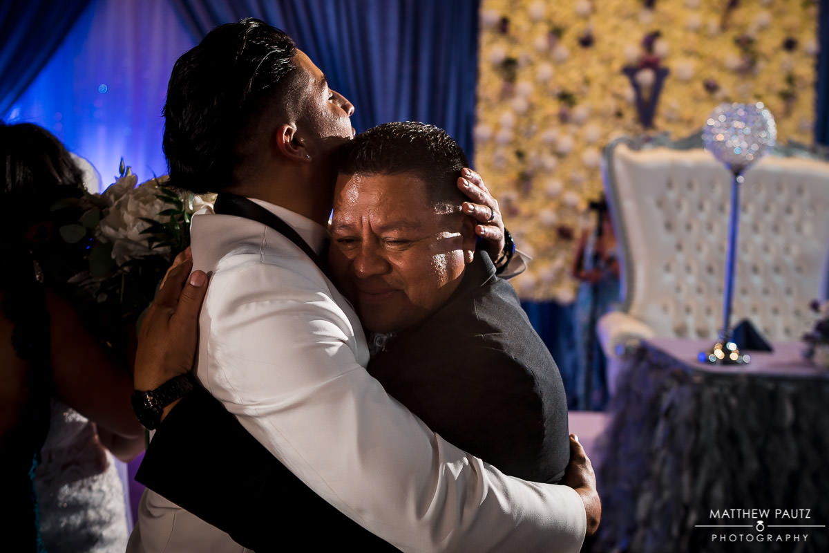 groom hugging his father during wedding reception