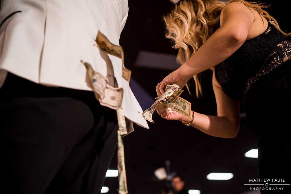wedding guest pinning money to groom's jacket