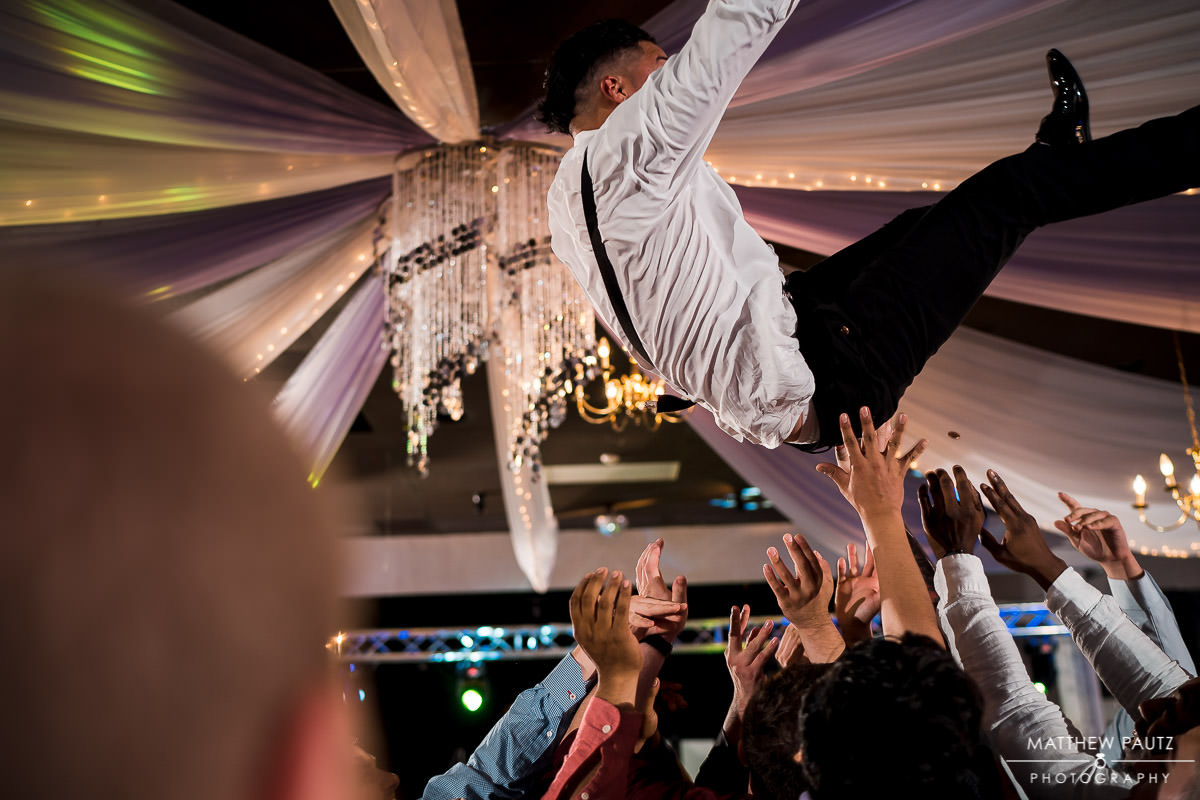 reception guests throwing groom into the air