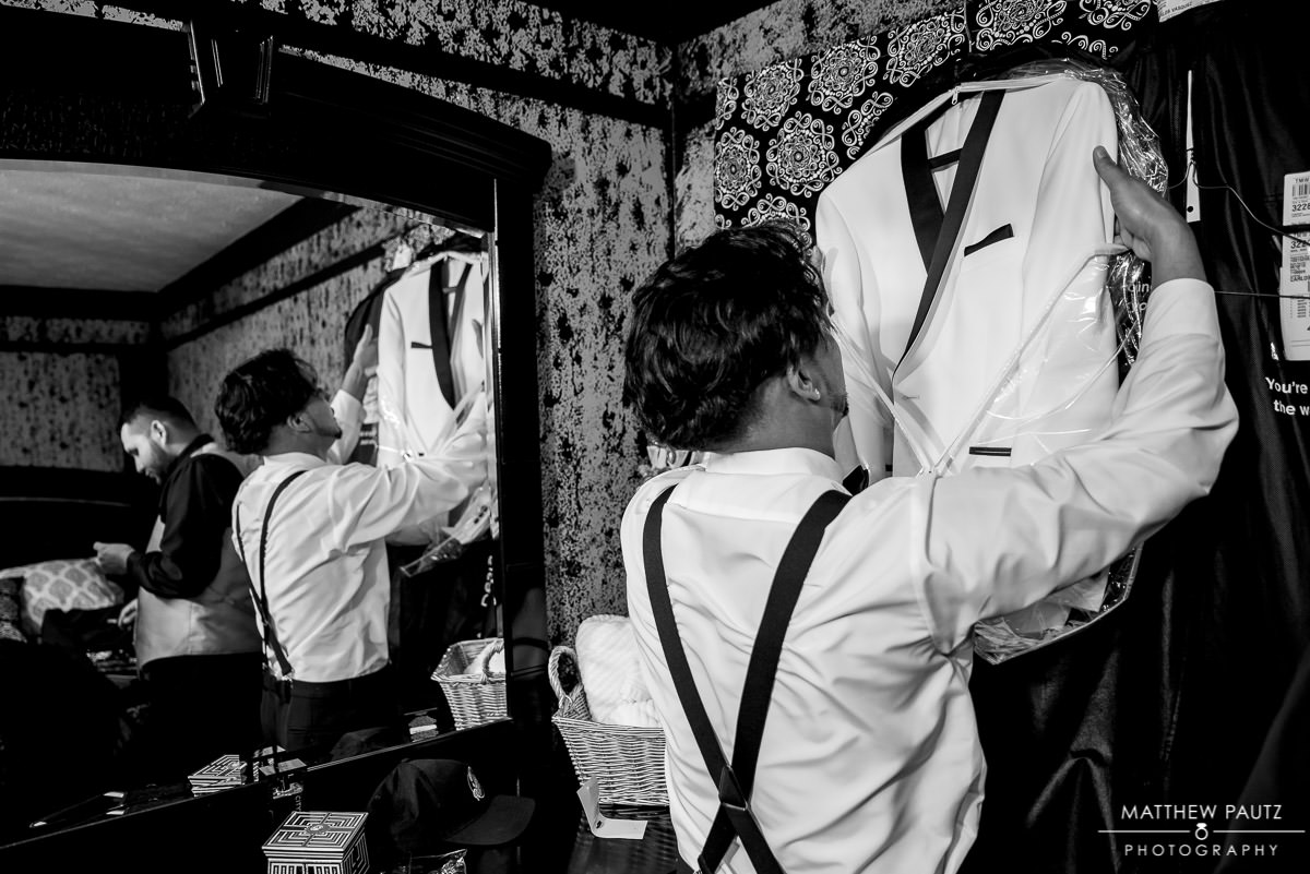 groom getting dressed in white tux
