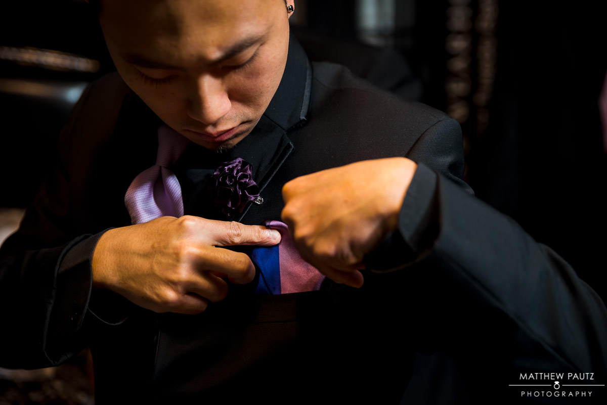 groomsman folding pocket square before wedding