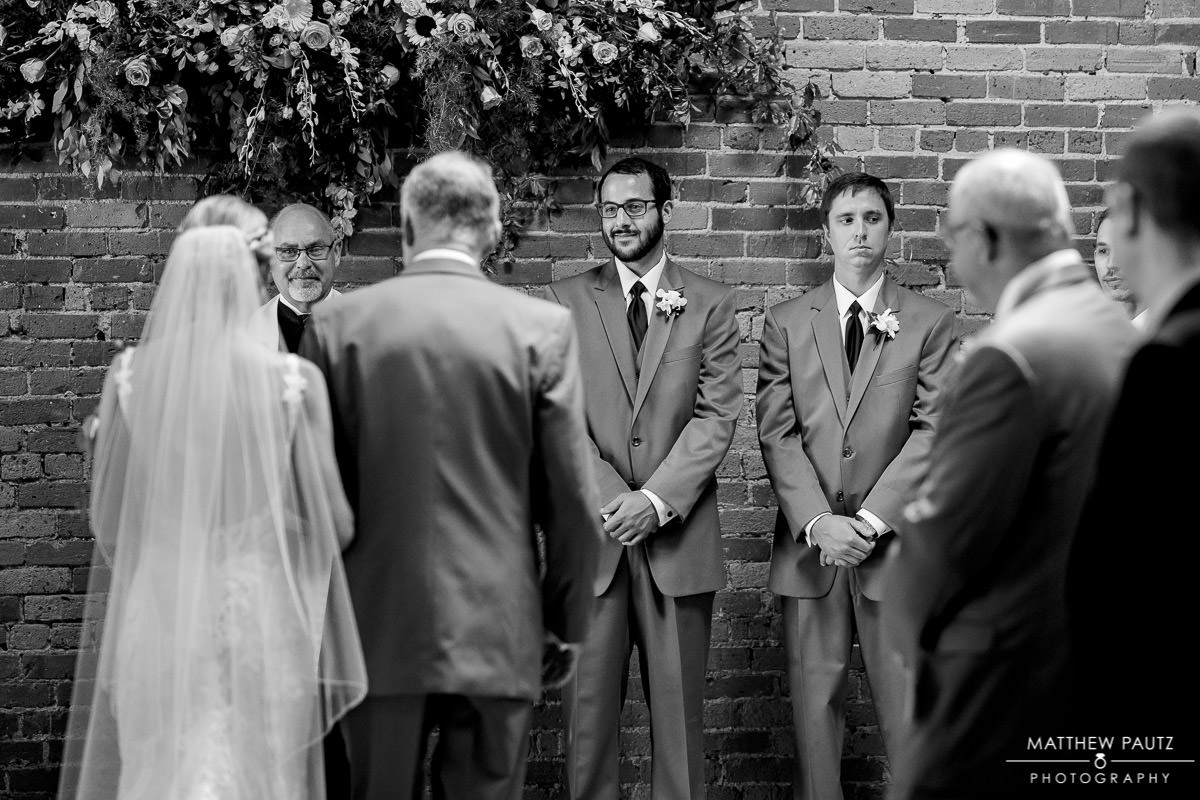 groom watching bride during wedding ceremony