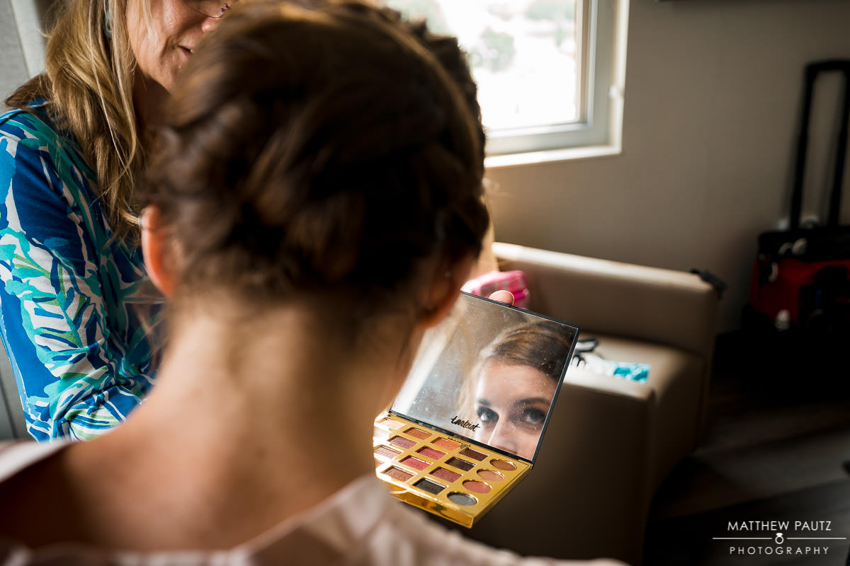 bridesmaid looking at makeup in mirror while getting ready for wedding