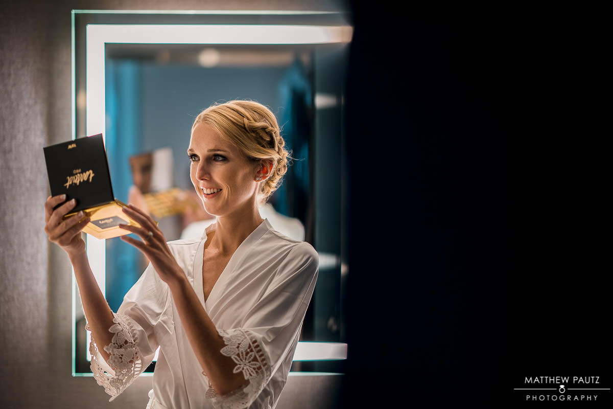 bride looking in mirror while getting ready for wedding