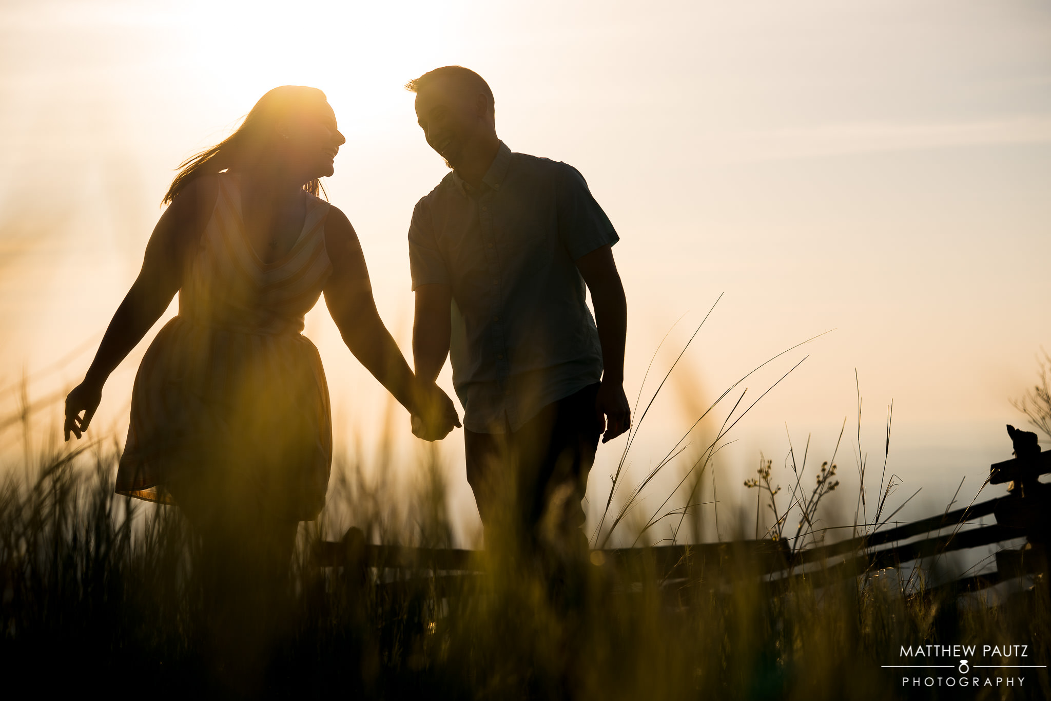 silhouette of engaged couple walking in tall grass at sunrise