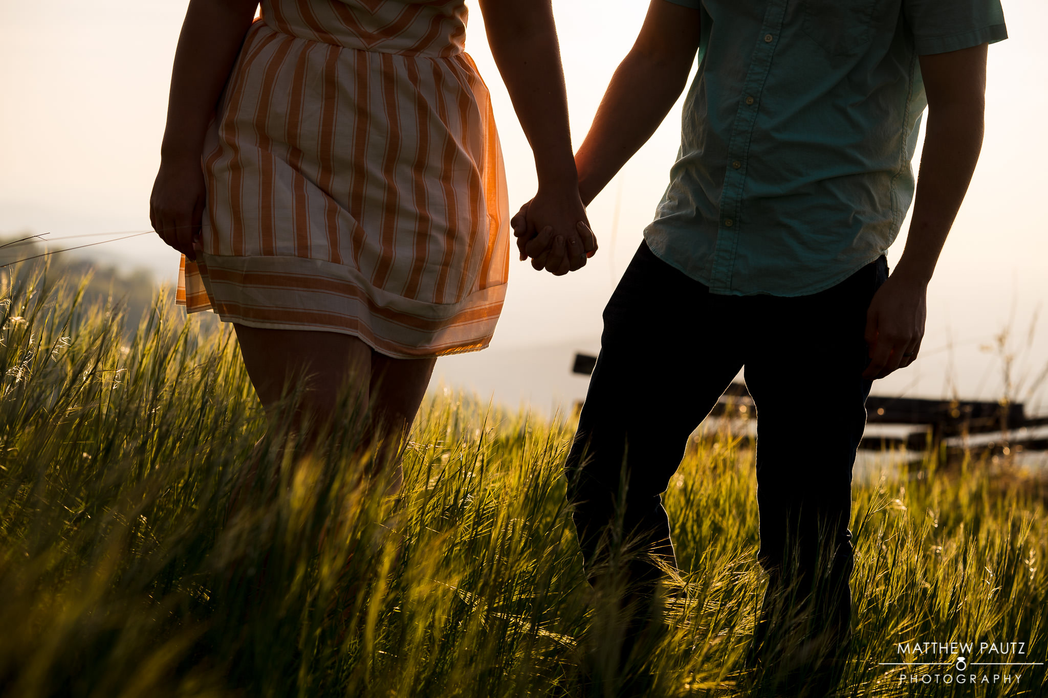 closeup of engaged couple holding hands at sunrise