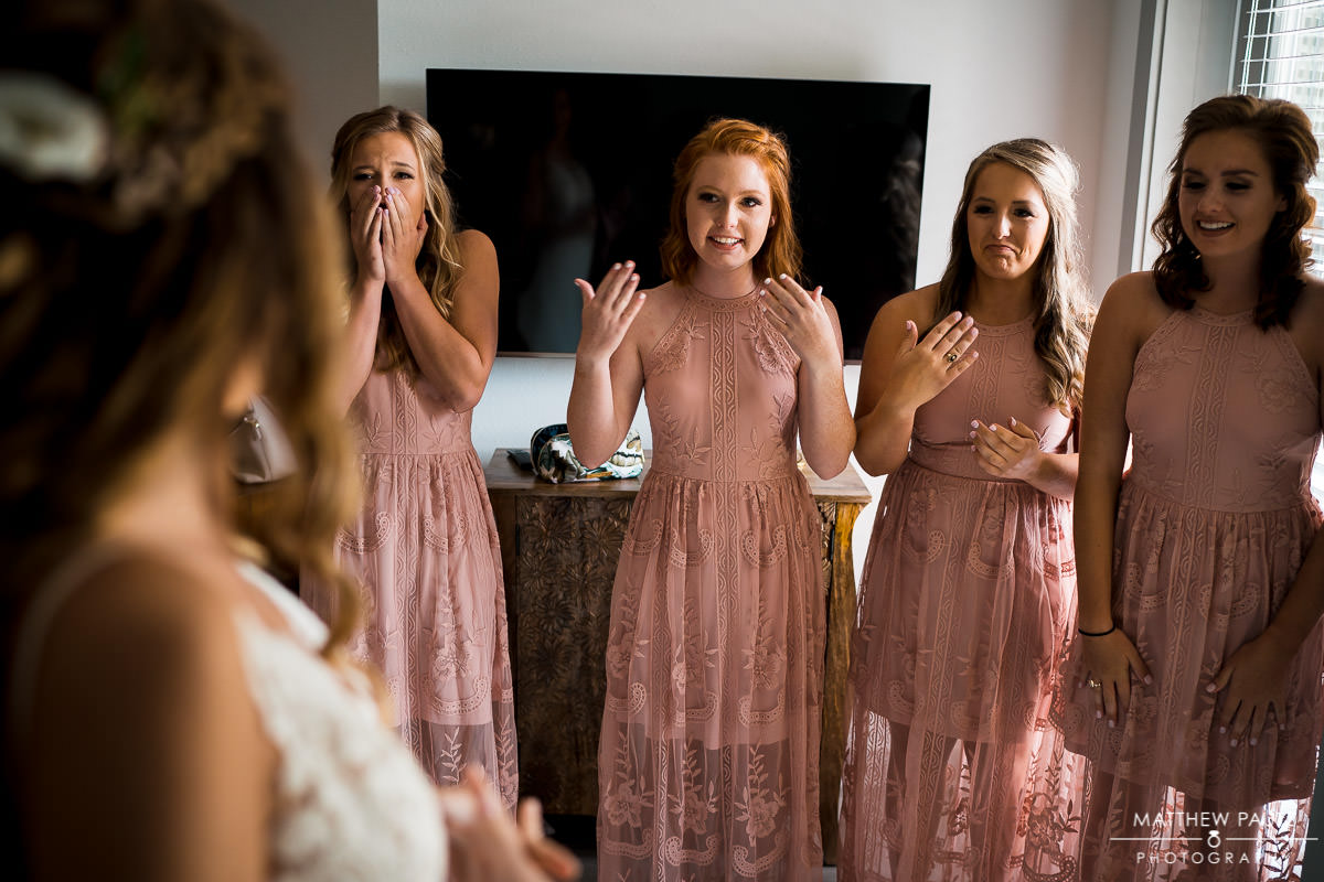 bridesmaids reacting to seeing the bride dressed for the first time