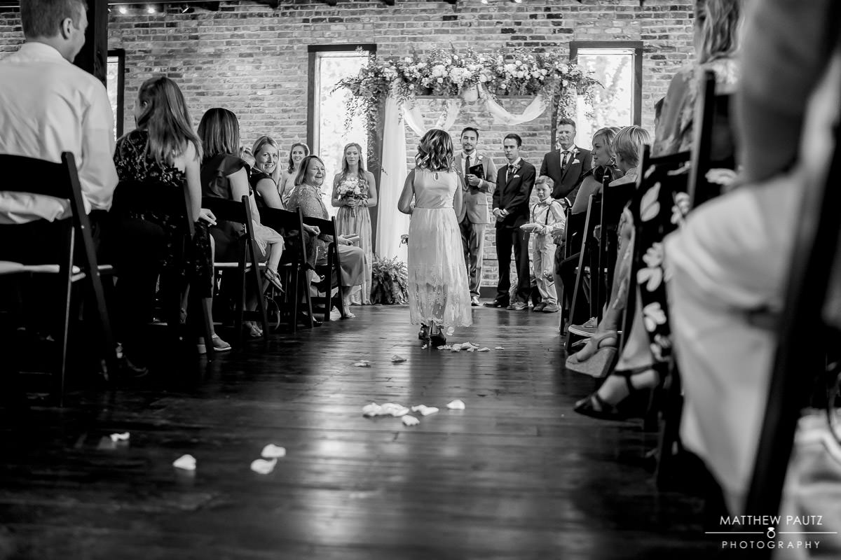 flower girl walking down the aisle at The Rutherford wedding ceremony