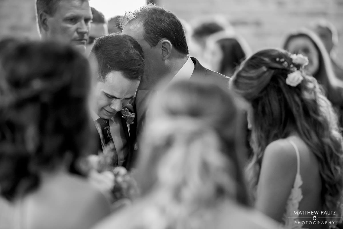 bride's father whispering in Groom's ear at wedding ceremony