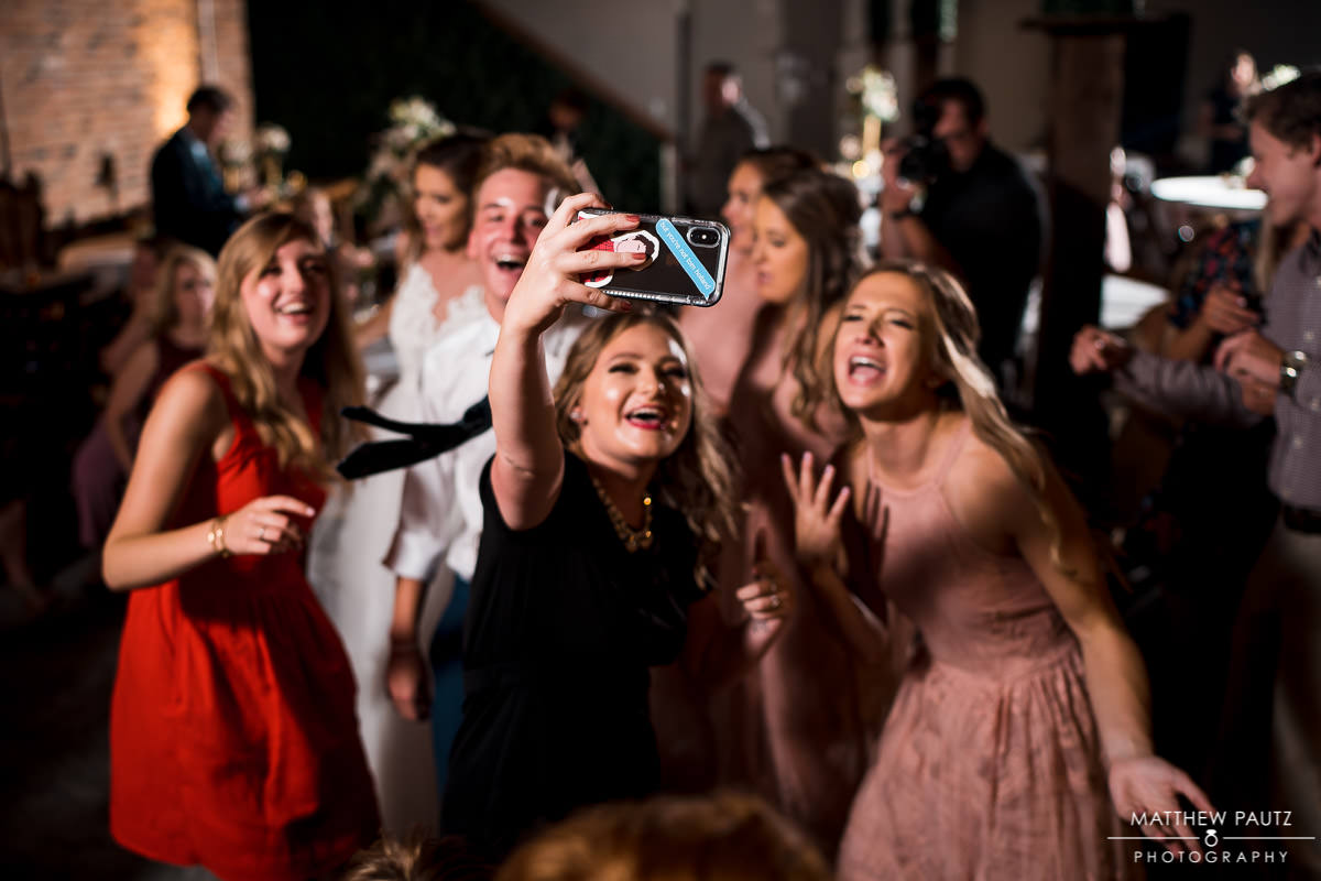 wedding guests having a good time and posing for selfie at wedding reception