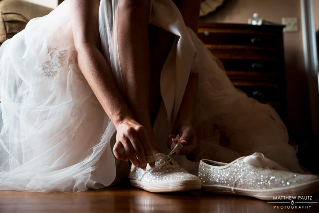 Bride putting on wedding shoes before ceremony