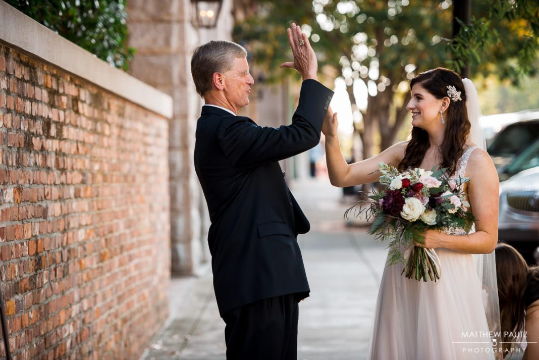 bride high fiving father before wedding