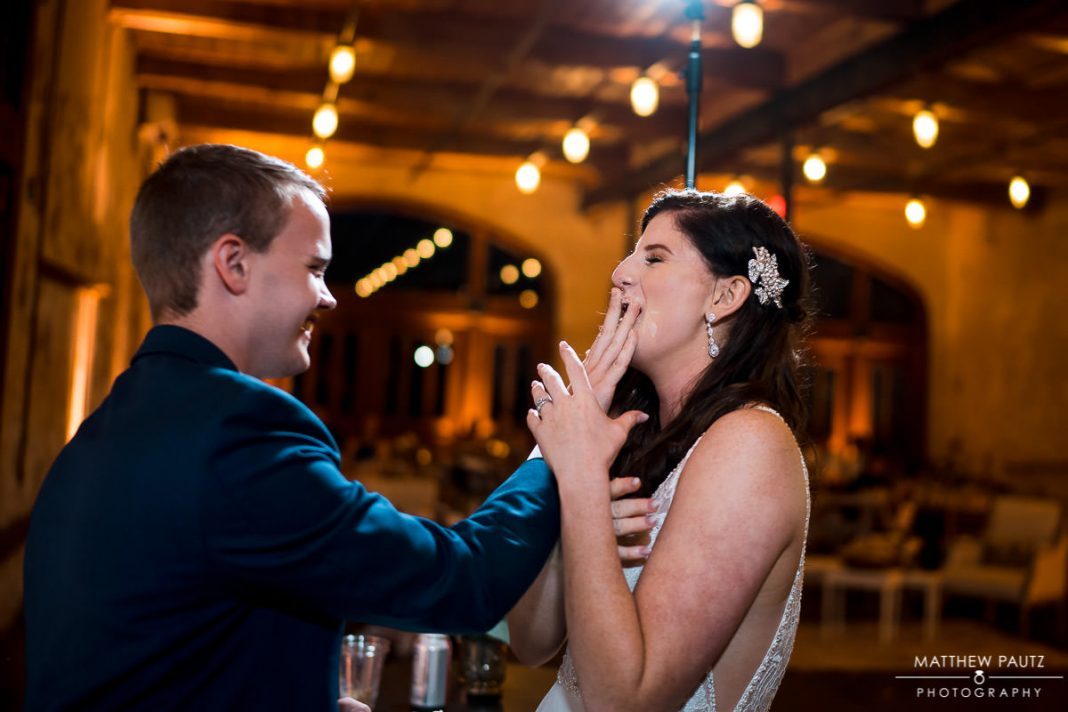 groom shoving cake in bride's mouth