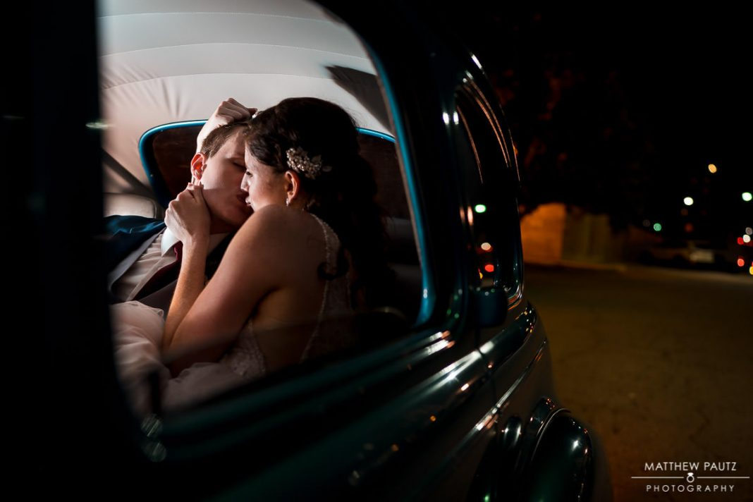 bride and groom kissing in classic car at night