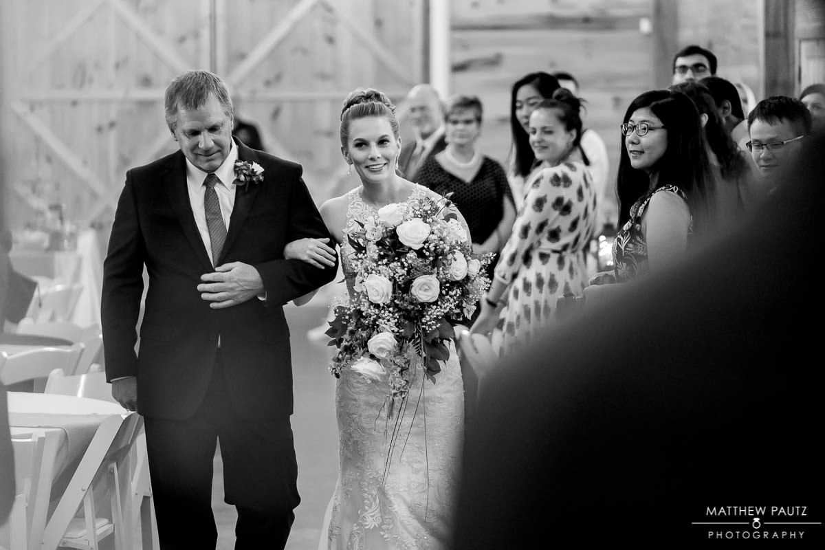 Bride and her father walking down aisle together at wedding ceremony