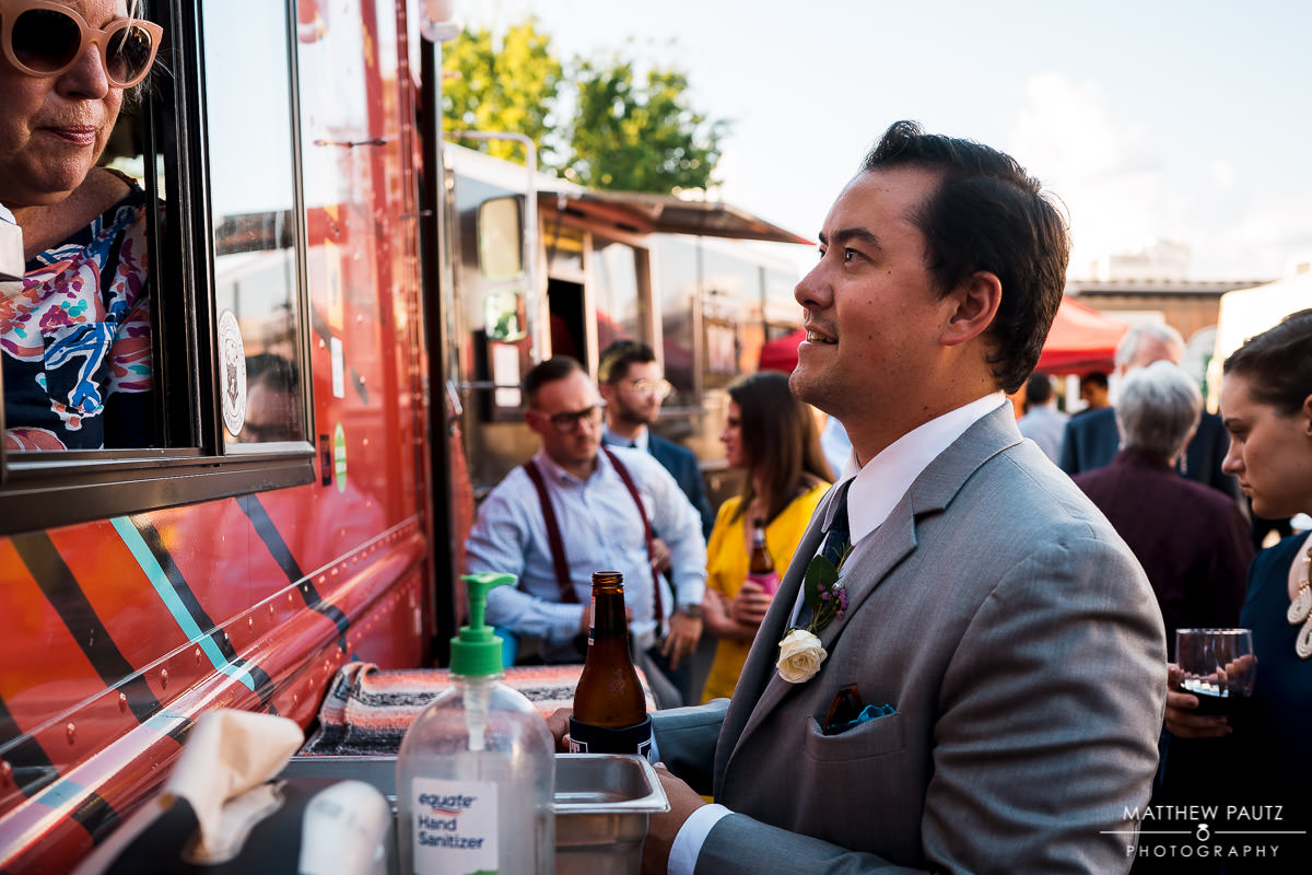 best man ordering from food trucks at wedding reception